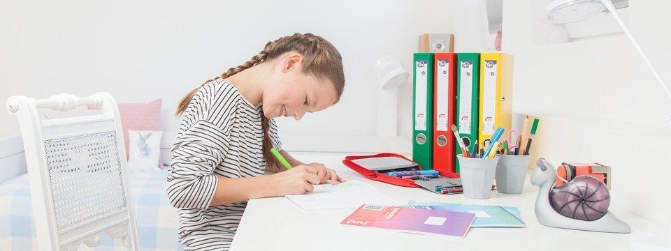 Mädchen schreibt in ein Heft
