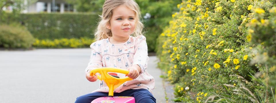 zweijähriges Mädchen auf Bobbycar
