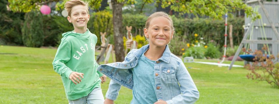 Neunjährige Kinder toben auf Wiese
